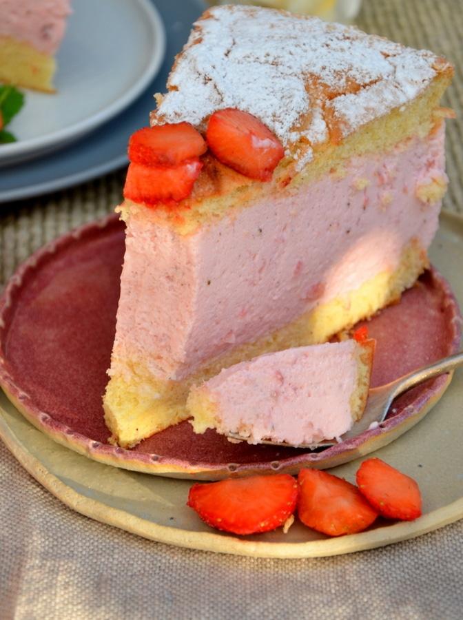 Erdbeer-Käsesahne-Torte, ein Stück auf Teller, ein Bissen mit Gabel abgestochen